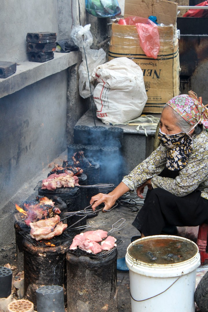 Woman cooking chicken in the street, Hanoi, Vietnam